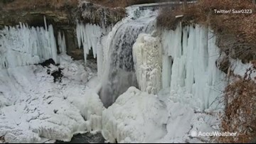 Stunning view of water racing over partially frozen waterfall