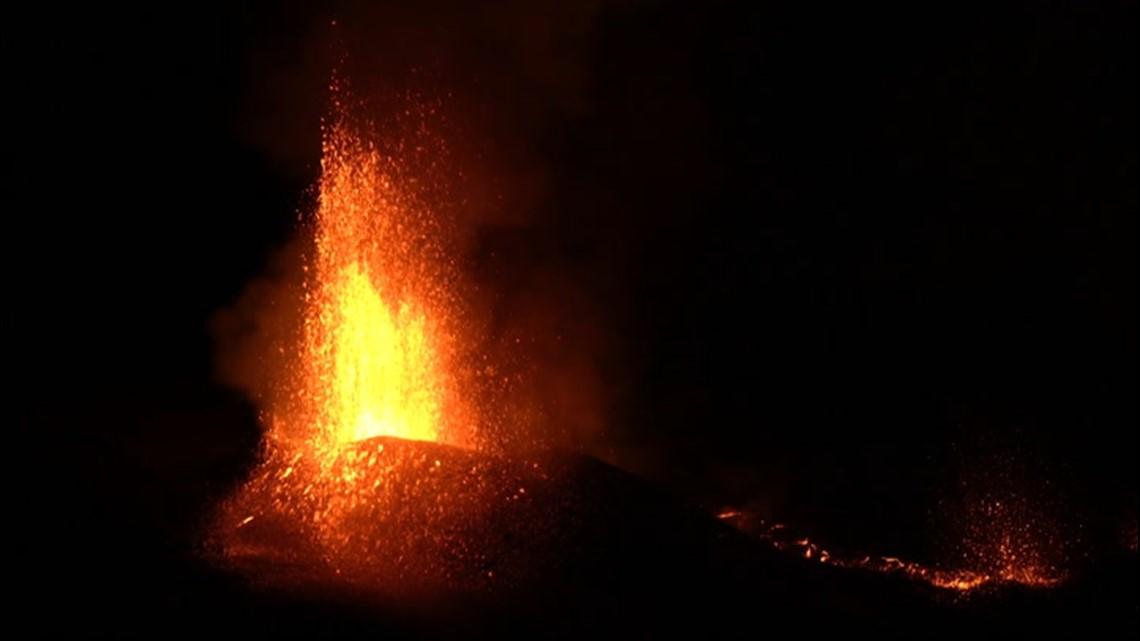 Hikers watch as volcano erupts