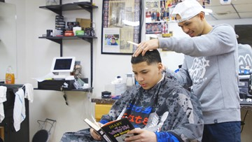 Barber pays kids to read a book during haircut to boost literacy, confidence