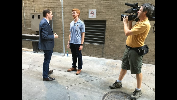 William O'Connor (center) talks with KVUE/Austin American-Statesman reporter Tony Plohetski (left) about his SUV dangling from the side of a downtown parking garage Sept. 9. KVUE photojournalist Scott Guest (right) filming the interview.