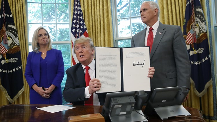 U.S. President Donald Trump, with Dept. of Homeland Security Secretary Kirstjen Nielsen & Vice President Mike Pence, displays an executive order he signed that will end the practice of separating family members.